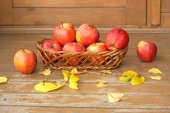 秋天静物画用在一个柳条筐和黄色叶子的红色苹果 免版税库存图片