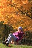 秋天颜色之前包围的微笑的小女孩 免版税图库摄影