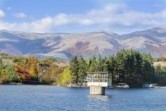 秋天颜色-与森林的山小山在湖附近 免版税库存图片