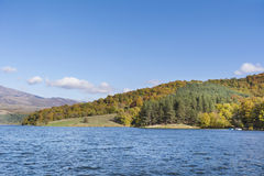 秋天颜色-与森林的山小山在湖附近 库存图片
