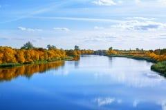 秋天风景、黄色叶子树在河岸天空蔚蓝的和白色云彩背景在好日子,反射在大海 库存照片