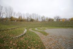 秋天风景在城市公园 石圆形剧场,位于沿中央平台的圈子 在黄色叶子的树, 库存图片