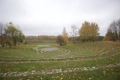 秋天风景在城市公园 石圆形剧场,位于沿中央平台的圈子 在黄色叶子的树, 免版税库存图片