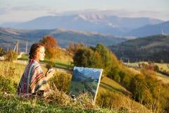 绘秋天风景的年轻艺术家 免版税库存照片
