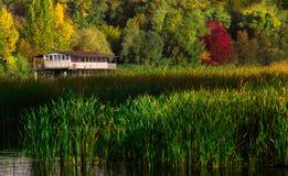 秋天风景-在水的老偏僻的房子 免版税库存图片