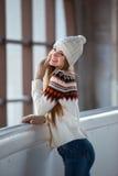 秋天,冬天画象:年轻微笑的妇女在一件温暖的羊毛羊毛衫、摆在的手套和的帽子穿戴了外面 免版税库存图片