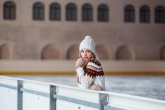秋天,冬天画象:年轻微笑的妇女在一件温暖的羊毛羊毛衫、摆在的手套和的帽子穿戴了外面 免版税库存照片