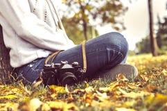 秋天,坐在有照相机的一个公园的女孩 免版税库存照片