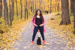 秋天,宠物,人概念-愉快加上笑与恶意嘘声的大小妇女 库存图片