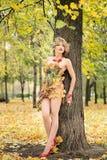 秋天,礼服的妇女有叶子的在公园 10月, 免版税库存图片