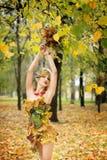 秋天,礼服的妇女有叶子的在公园 10月, 免版税图库摄影