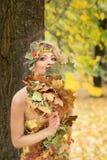 秋天,礼服的妇女有叶子的在公园 10月, 免版税库存照片