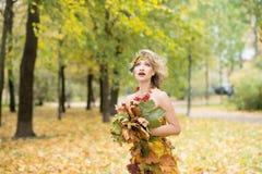 秋天,礼服的妇女有叶子的 10月 室外 图库摄影