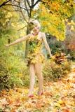 秋天,礼服的妇女有叶子的 10月 免版税图库摄影