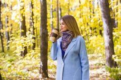 秋天,自然,人概念-年轻深色的妇女饮料咖啡在秋天公园 库存图片