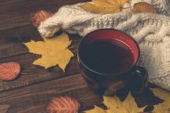 秋天,黄色和橙色秋天离开,热的茶,在木土气背景的温暖的围巾 库存图片