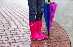 秋天 保护在雨中 穿桃红色胶靴的妇女(女孩)和有伞 图库摄影