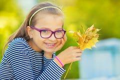 秋天 在她的手上拿着秋天槭树花束一个微笑的女孩的画象离开 库存图片