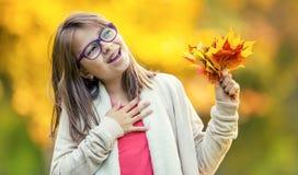 秋天 在她的手上拿着秋天槭树花束一个微笑的女孩的画象离开 免版税库存照片