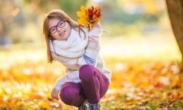 秋天 在她的手上拿着秋天槭树花束一个微笑的女孩的画象离开 免版税库存图片