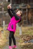 秋天/春天衣裳的小女孩在电话做selfie 库存图片