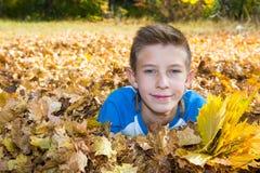 秋天 有叶子的男孩少年在秋天 免版税图库摄影