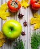 秋天结果实-绿色苹果计算机、柿子、黄色叶子和香料在一张木桌上 库存照片