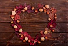 以秋天绯红色叶子的形式心脏的平的位置框架, 库存照片