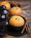 秋天主题的碗筷 黑瓦器,长的肉桂条,在简单的木背景的小成熟南瓜 库存图片