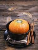 秋天主题的碗筷 黑瓦器,长的肉桂条,在简单的木背景的小成熟南瓜 免版税库存图片