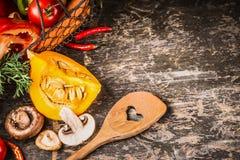 秋天素食烹调用南瓜、蘑菇和菜在土气木背景与烹调匙子,顶视图 健康 免版税图库摄影
