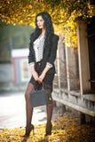 秋季时尚射击的可爱的少妇 摆在公园的黑白成套装备的美丽的时兴的夫人 库存照片