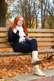 秋季的女孩在城市公园、黄色树和下落的叶子听在音频球员的音乐有耳机的,坐长凳 库存照片