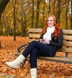 秋季的女孩在城市公园、黄色树和下落的叶子听在音频球员的音乐有耳机的,坐长凳 库存图片