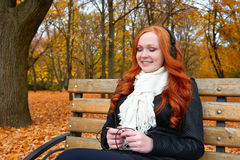 秋季的女孩在城市公园、黄色树和下落的叶子听在音频球员的音乐有耳机的,坐长凳 免版税库存照片