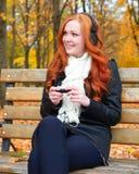 秋季的女孩在城市公园、黄色树和下落的叶子听在音频球员的音乐有耳机的,坐长凳 图库摄影