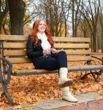 秋季的女孩在城市公园、黄色树和下落的叶子听在音频球员的音乐有耳机的,坐长凳 免版税库存图片