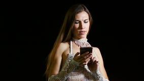 种族东方服装的女孩舞蹈家在晚上使用室外的智能手机 股票录像