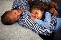 种族休眠在楼层上的父亲和小女孩 图库摄影