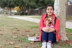 种族十几岁的女孩使用与狗的在一棵树下在有书的公园和学校挑运 免版税库存照片
