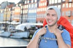种族背包徒步旅行者微笑在史诗Nyhavn的,哥本哈根,丹麦 免版税库存照片