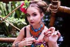 种族衣裳的女孩在有蛇的热带庭院里 免版税库存照片