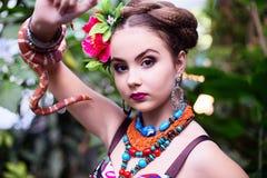 种族衣裳的女孩在有蛇的热带庭院里 库存照片