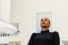 种族黑人女性患者坐的查寻在等待她的牙医的牙齿椅子 图库摄影