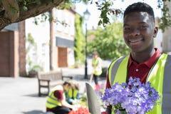 种植和整理共同花的小组有用的少年 免版税库存照片