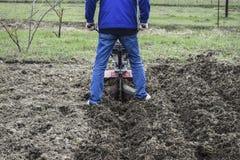 种植在下的土豆步行在拖拉机后 图库摄影