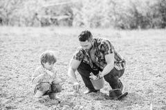 种植在地面的父亲和儿子花 r 富有的自然土壤 Eco?? 小男孩儿童帮助父亲 库存图片