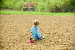 种植在领域 种植幼木 种植在领域的小男孩花 在农场的乐趣时间 E 库存照片