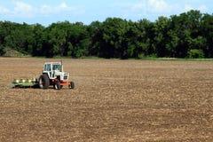 种植大豆豆领域的拖拉机 免版税库存照片