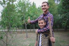 种植家谱 种植树的愉快的年轻人,当他的帮助他时的弟弟 变褐环境叶子去去的绿色拥抱本质说明说法口号文本结构树的包括的日地球 我们做着 库存照片